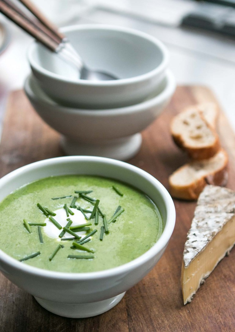 watercress soup in a bowl with a hunk of cheese