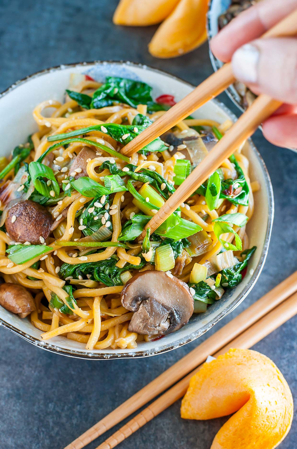 vegan noodles with spinach, mushrooms and leeks in a bowl with chopsticks