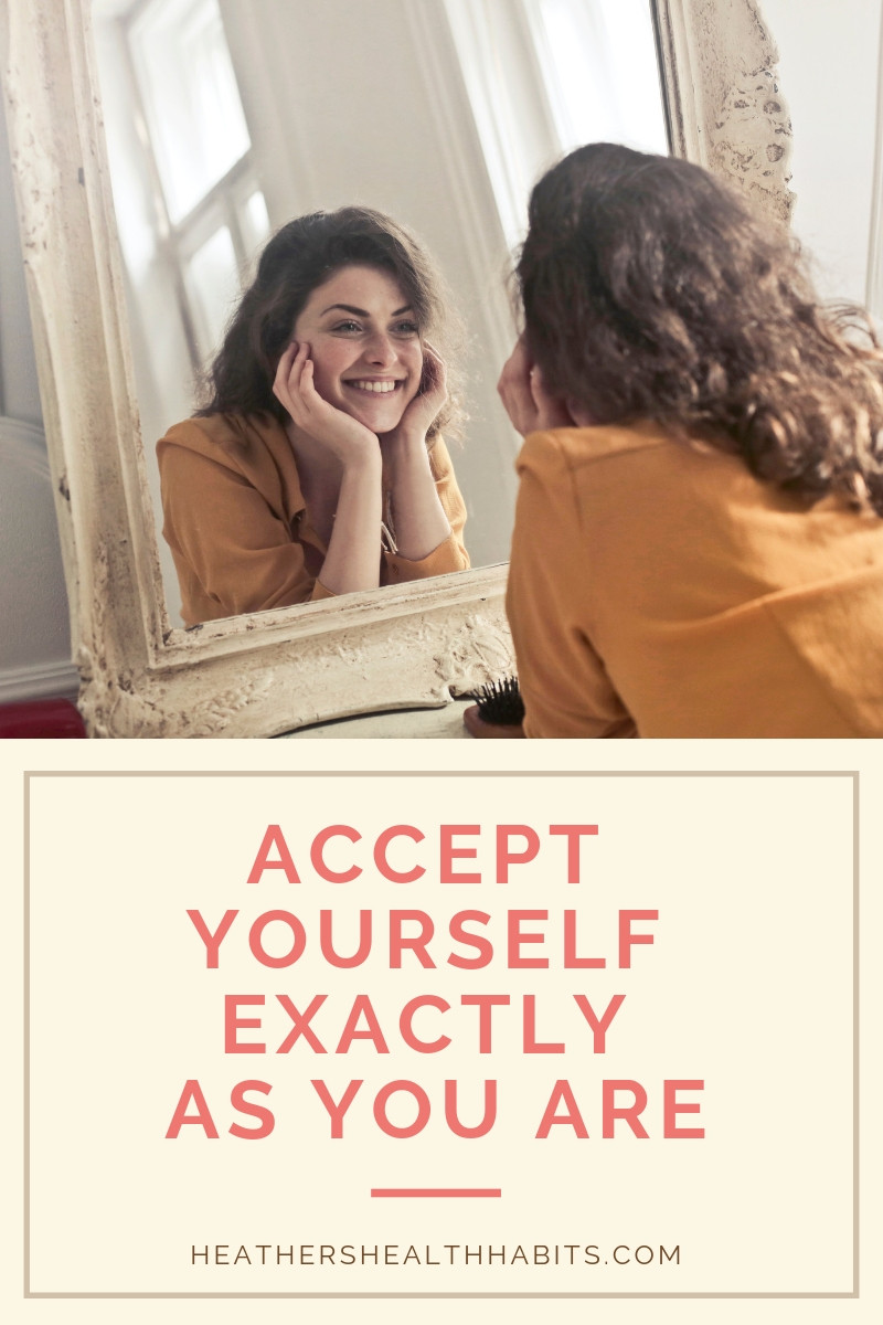 woman looking in mirror smiling at herself