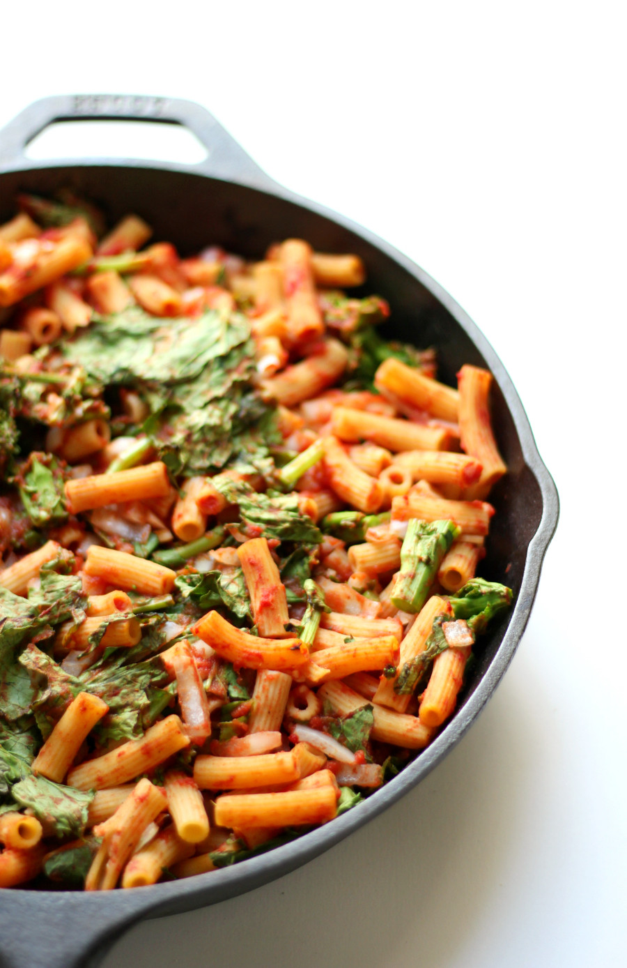 skillet full of gluten free penne pasta with tomatoes and broccoli rabe