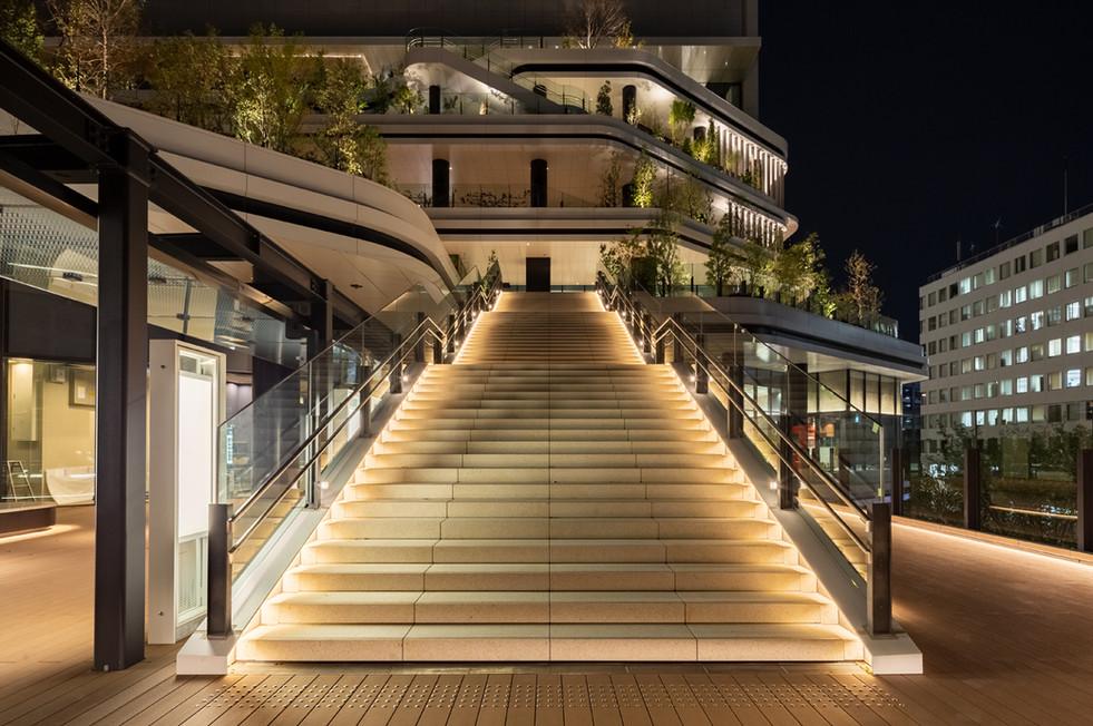 スキップテラス2階から3階へ上がる階段を見上げる  両側の足元のライン状の光とブラケットライトが人々を招き入れる。