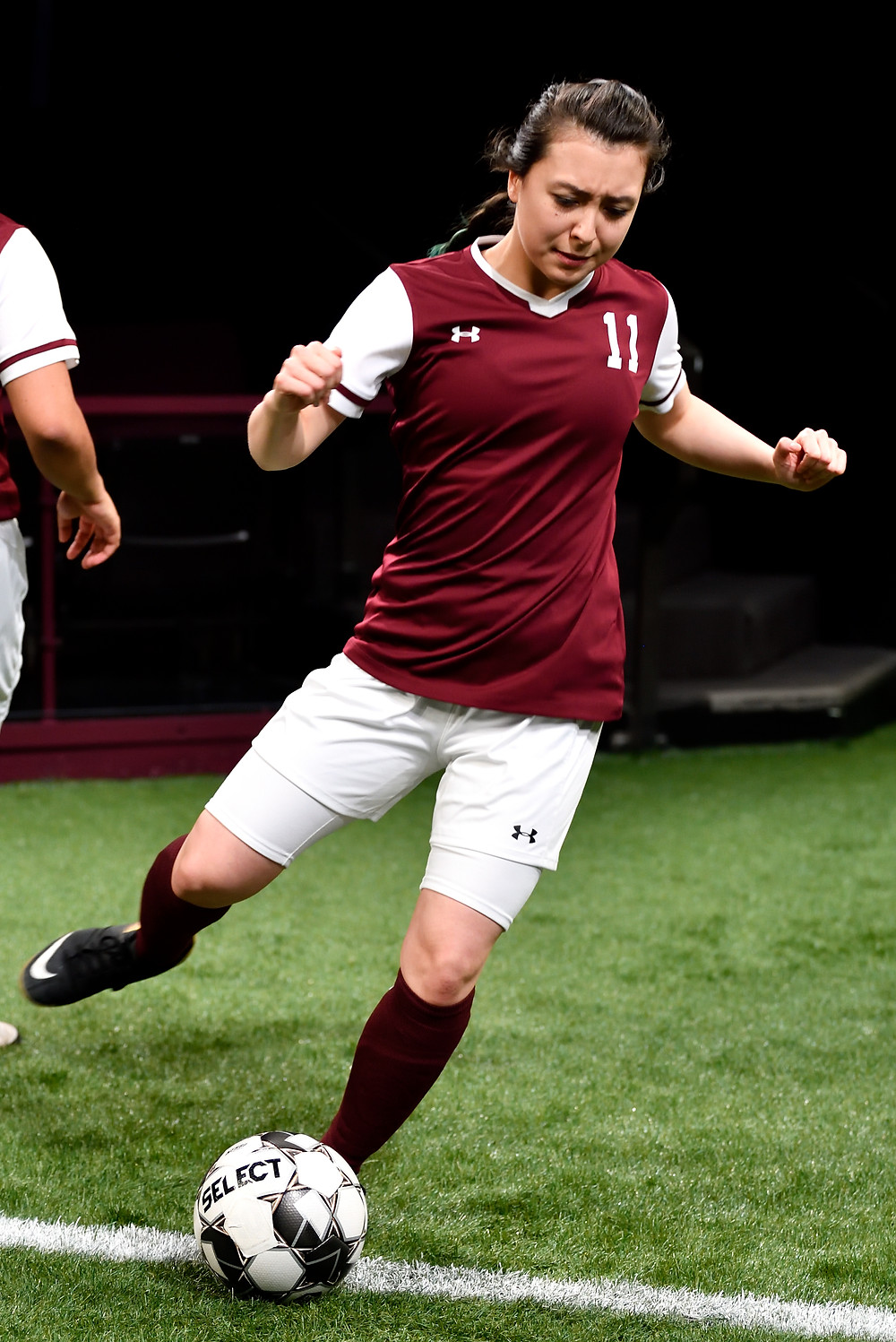"""Alex Lin as #11 in Actors Theatre of Louisville's production of Sarah DeLappe's """"The Wolves"""" kicks a soccer ball. Photo by Jonathan Roberts."""