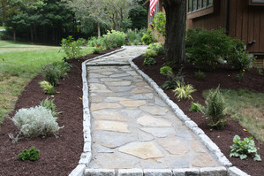 Bordered by granite cobblestone, this natural stone walkway is a welcoming entry to the front door.
