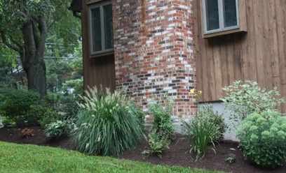 A brick chimney is enhanced by grasses, which left up during the winter add seasonal interest to the garden.
