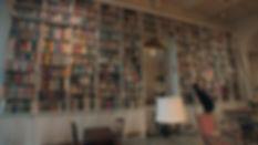 Adam Weinberger examining a bookshelf -