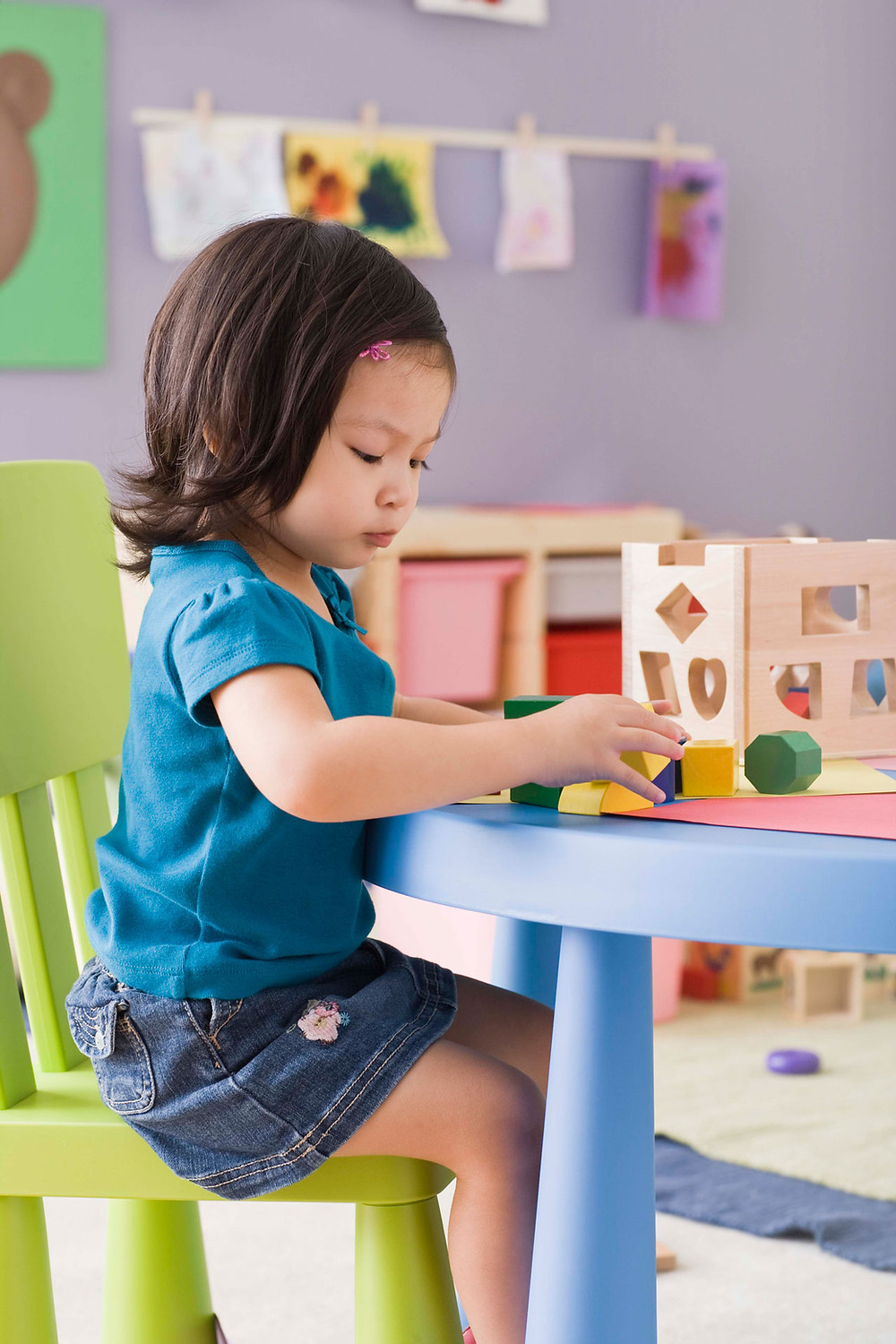 Child at nursery table, concentrating on playing alone with shapes.