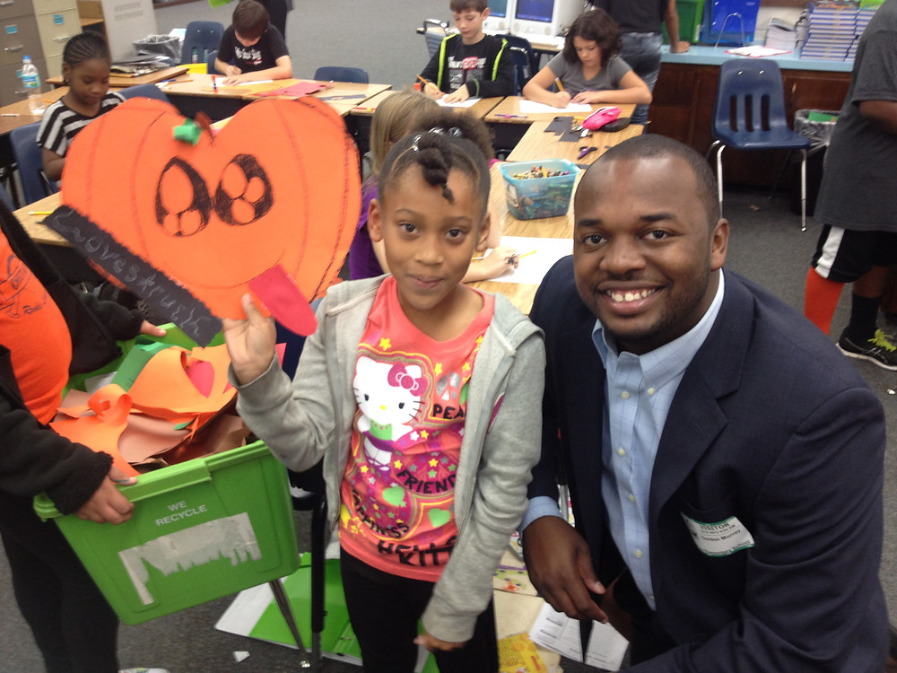 Young student holds up drawing of a pumpkin next to G.C.