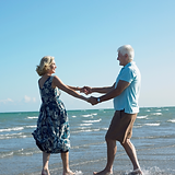 old couple dancing on beach in love happy