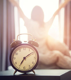 Closeup alarm clock having a good day with background happy woman stretching in bed after