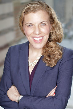Photo of Regina. A white woman with blue eyes wearing a blazer confidently smiles at the camera with her arms crossed.