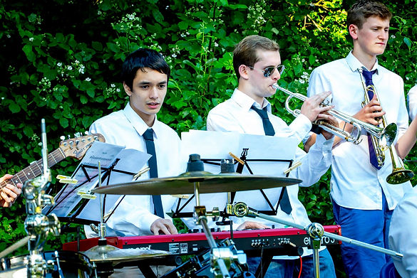 Photo, taken by Oliver Bowering, picutres from left to right, Christopher Webb, Josh Stockton, and Seb Skelly, all playing their instruments (keyboard, piano, tumpet, guitar, drums, cymbals) during University of Surrey Big Band Boat Tour.