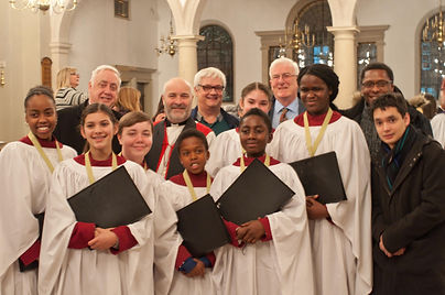 Christophe Webb, chorister and music theory tutor, and personal assistant to Jonathan Venner BEM, stands alongside pupils whom he helped to pass their Dean's Bronze Award. They stand in Brentwood Cathedral, happily wearing their bronze medals, in front of Mr. Venne, Mike Power (Minister for St. Edward the Confessor Church, Romford), and other officials.