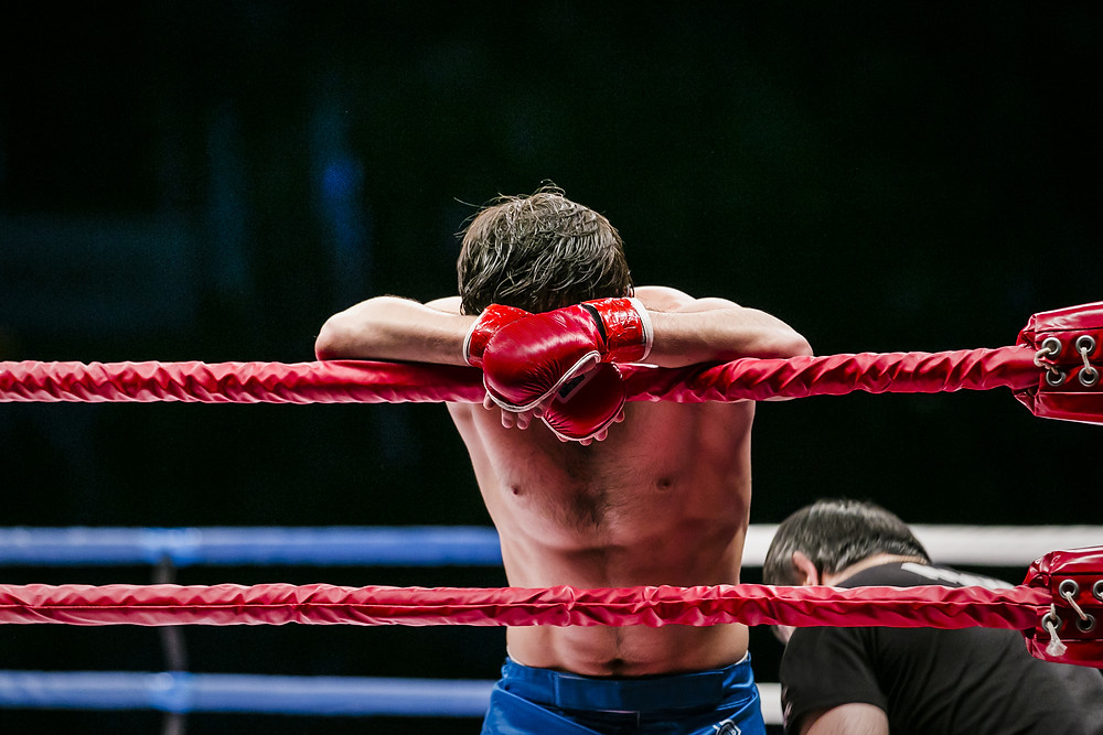 boxer resting his head on the ropes of the ring, looking defeated, upset, tired,