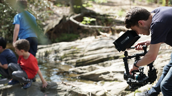 Ben filming by a river