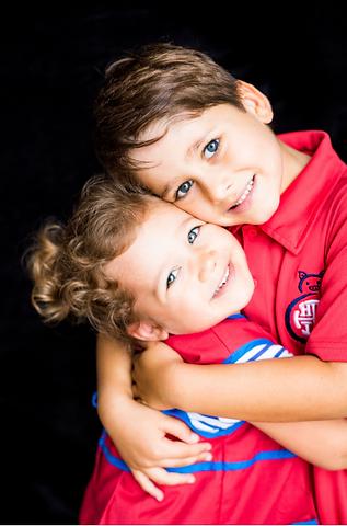 Siblings hugging and lookig at the camera