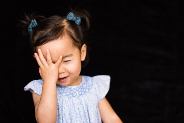 Little girl playing peek a boo