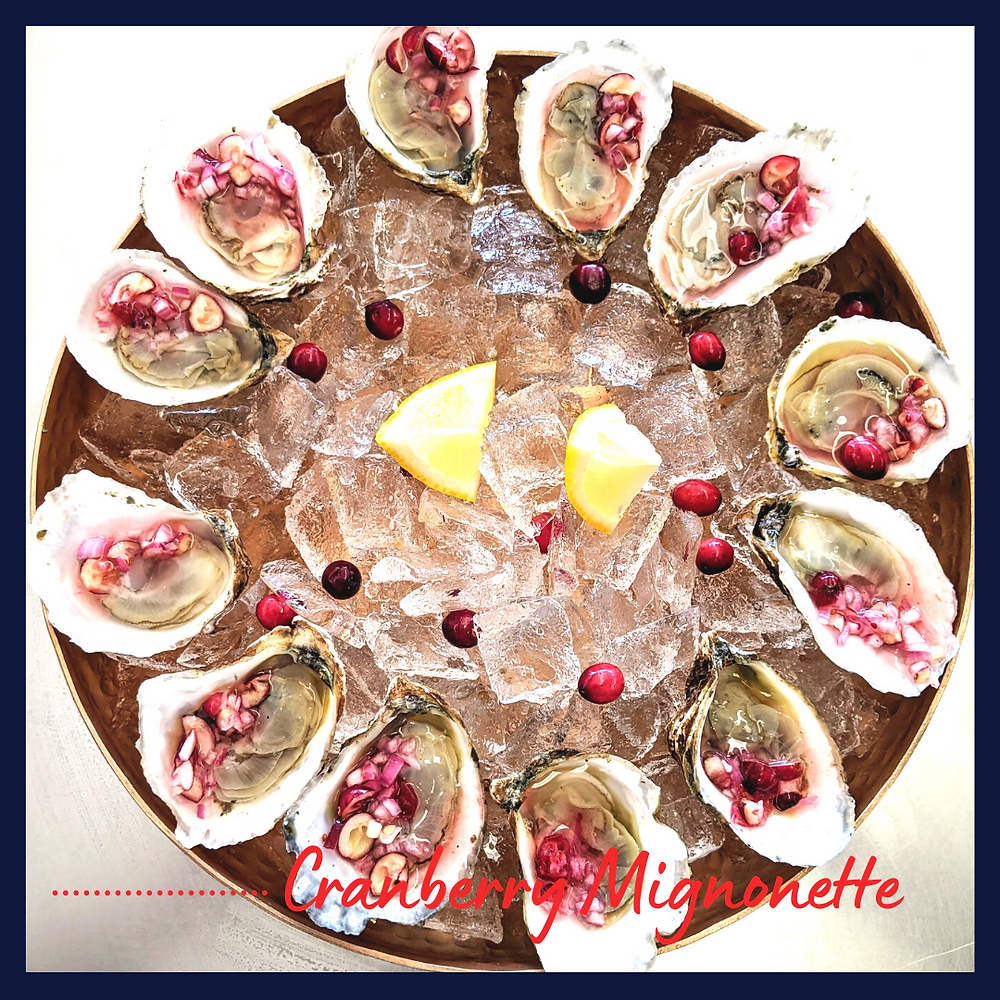 Oysters with cranberry mignonette on ice in copper serving tray with lemon