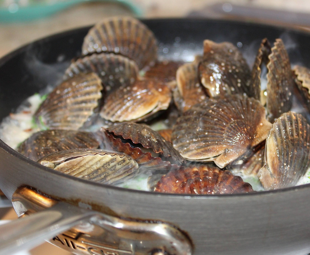 A pan of Niantic Bay Scallops being steamed in a garlic wine sauce.