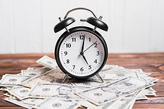alarm-clock-spread-currency-notes-wooden