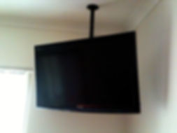Samsung LCD TV hanging from ceiling; black; white walls; window; TV Wall Mounting