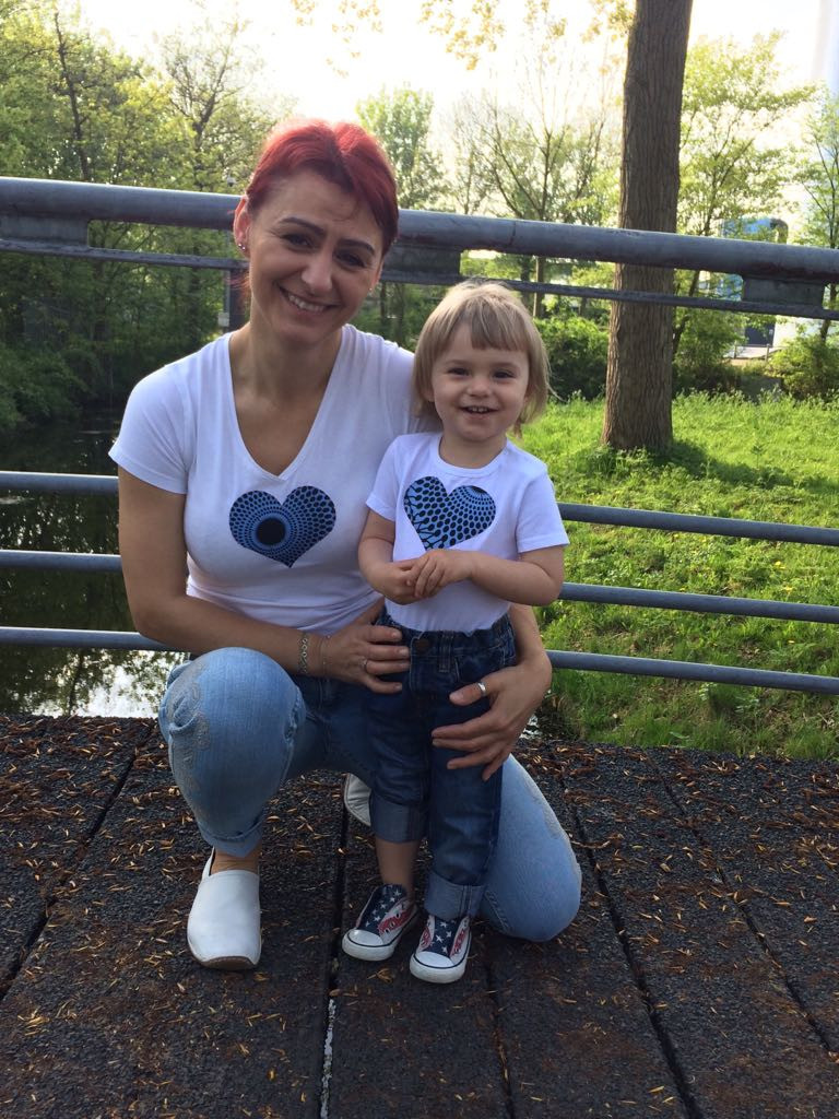Karolina with little Mia in their Wakanda Tees with heart patches made from recycled fabrics by Karolina herself.