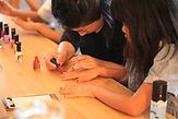 女の子の手に胡粉ネイルを塗っている女性