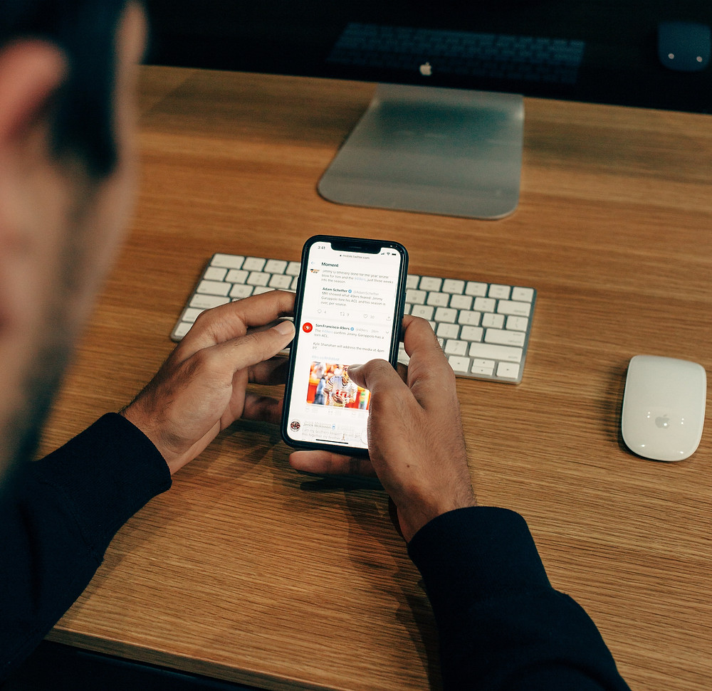 Man using app on iPhone at his desk.