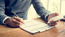man-writing-insurance-application-form-c