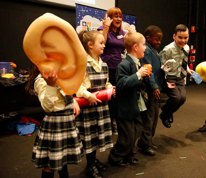 Science safari presenter has Six volunteers demonstrating how we hear sound