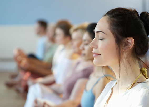 lady meditating during a group wellness yoga session