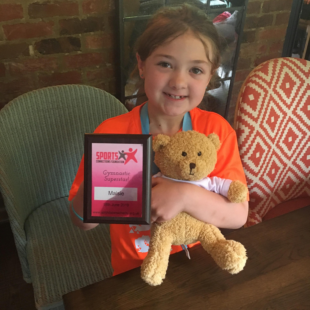 Maisie proudly showing off her trophy and teddy bear