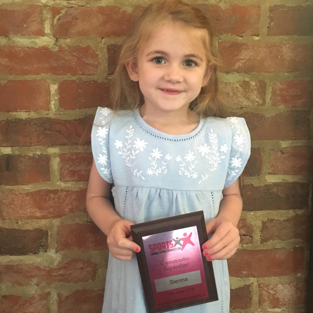 Sienna was very happy to receive her trophy for gymnastic excellence!