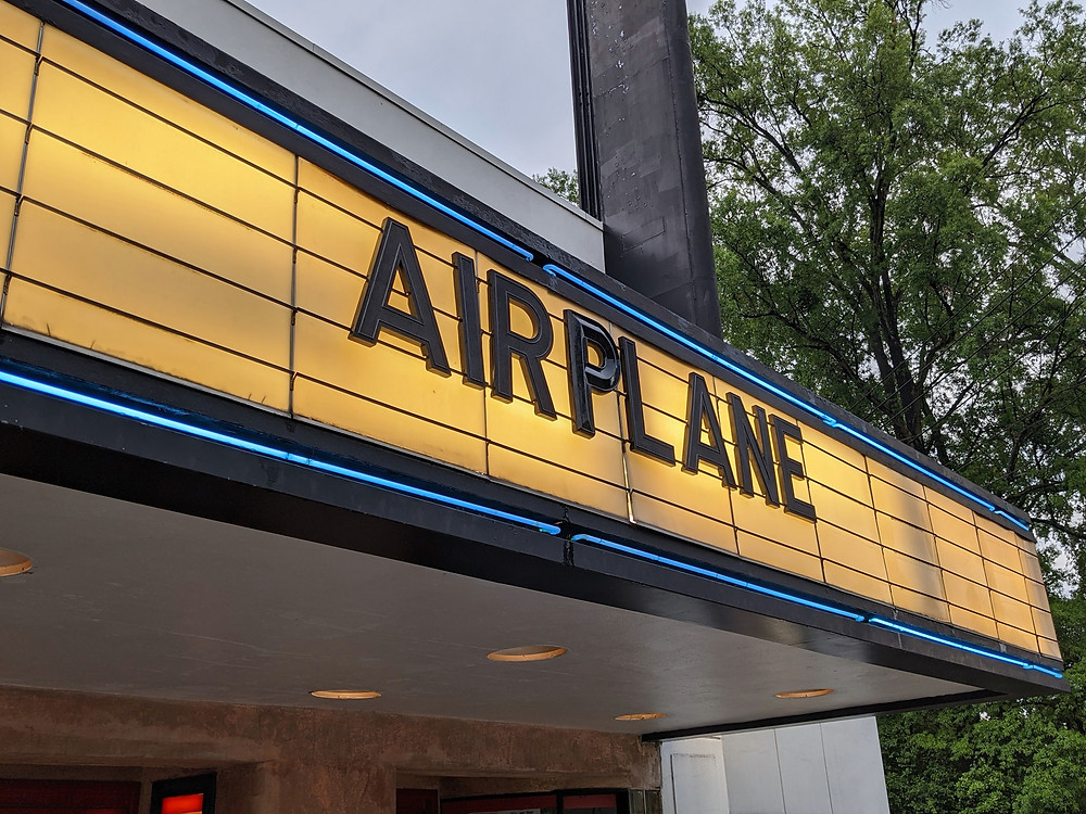 """The billboard outside the theater, reading """"Airplane"""""""