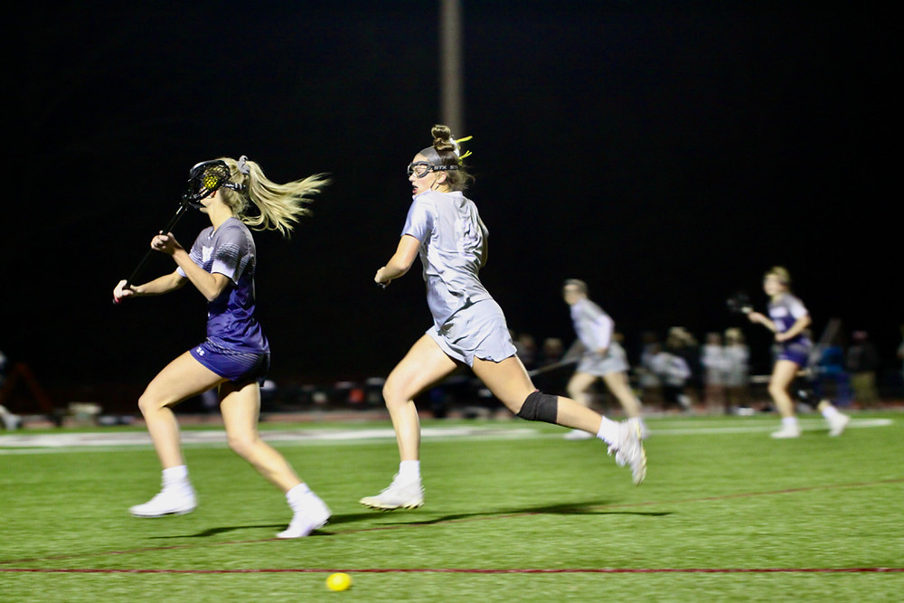 Two lacrosse players run on the field