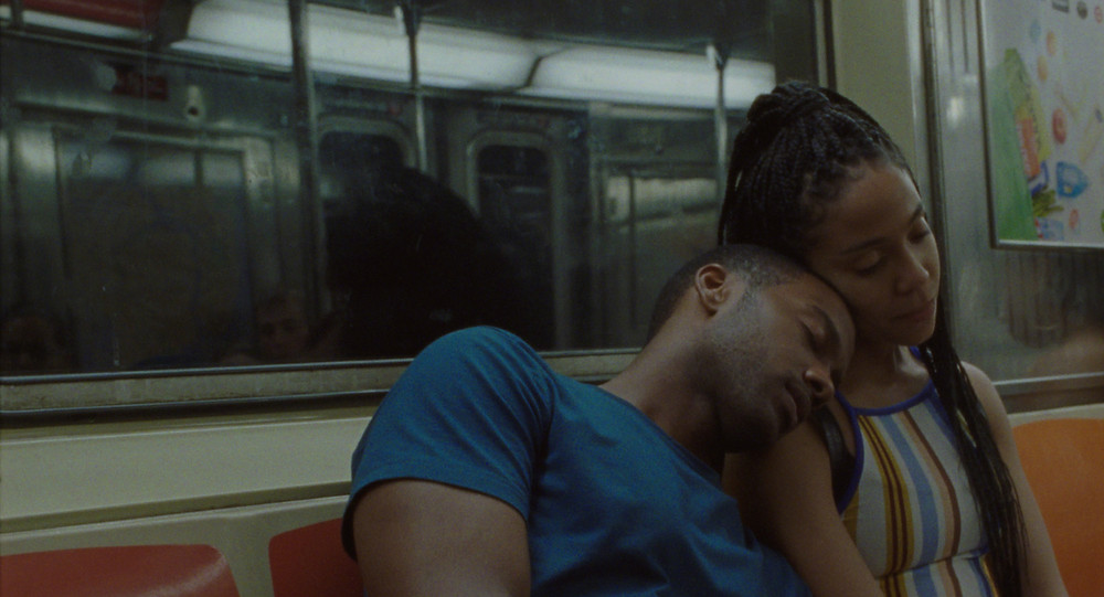 A Black man and woman sitting in a subway car