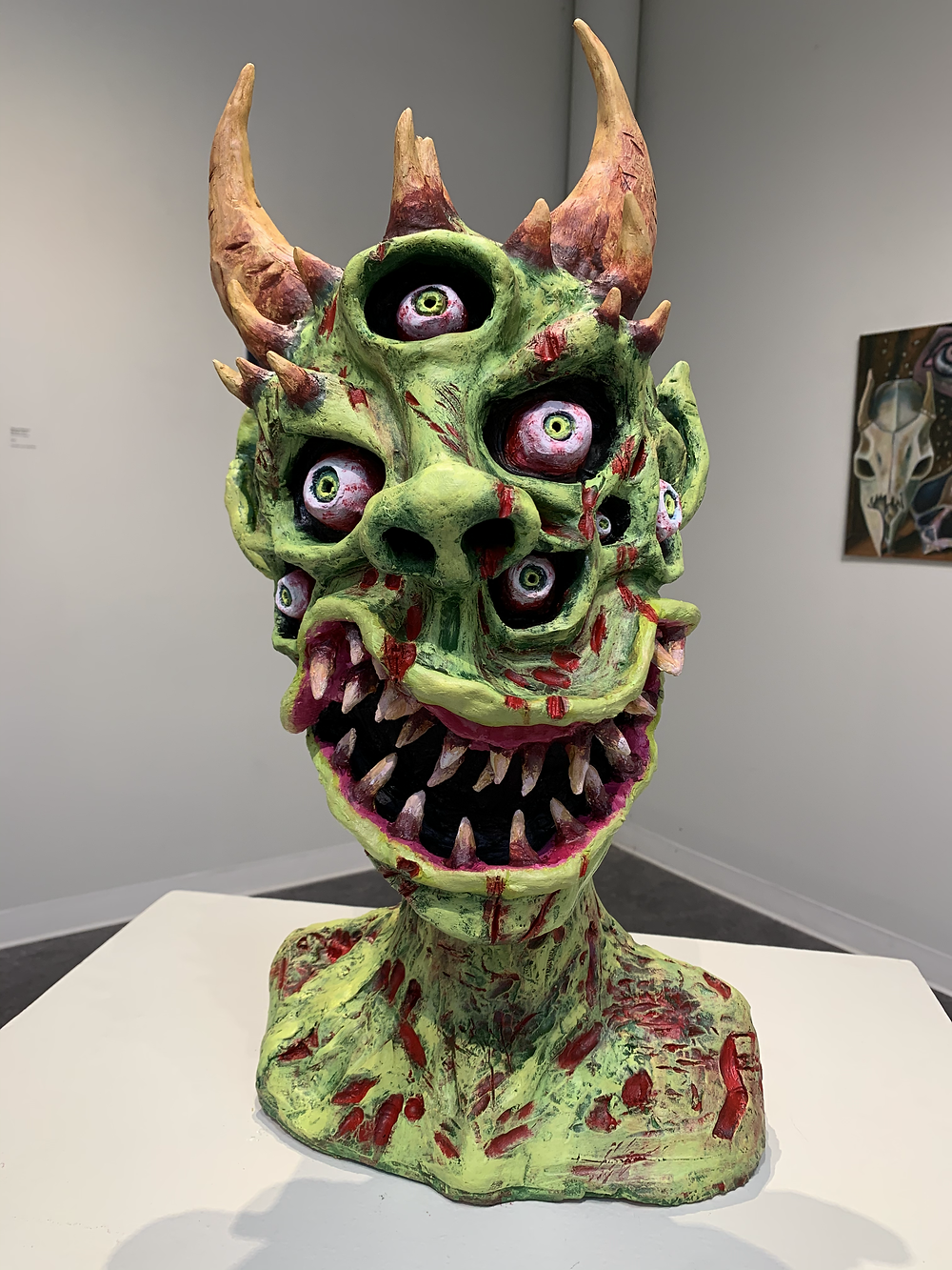The bust of a green monster with three eyes and horns and many jagged teeth, and cuts all over his body