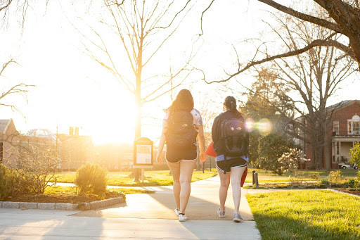 Two students with backpacks on walking into the sunset on campus