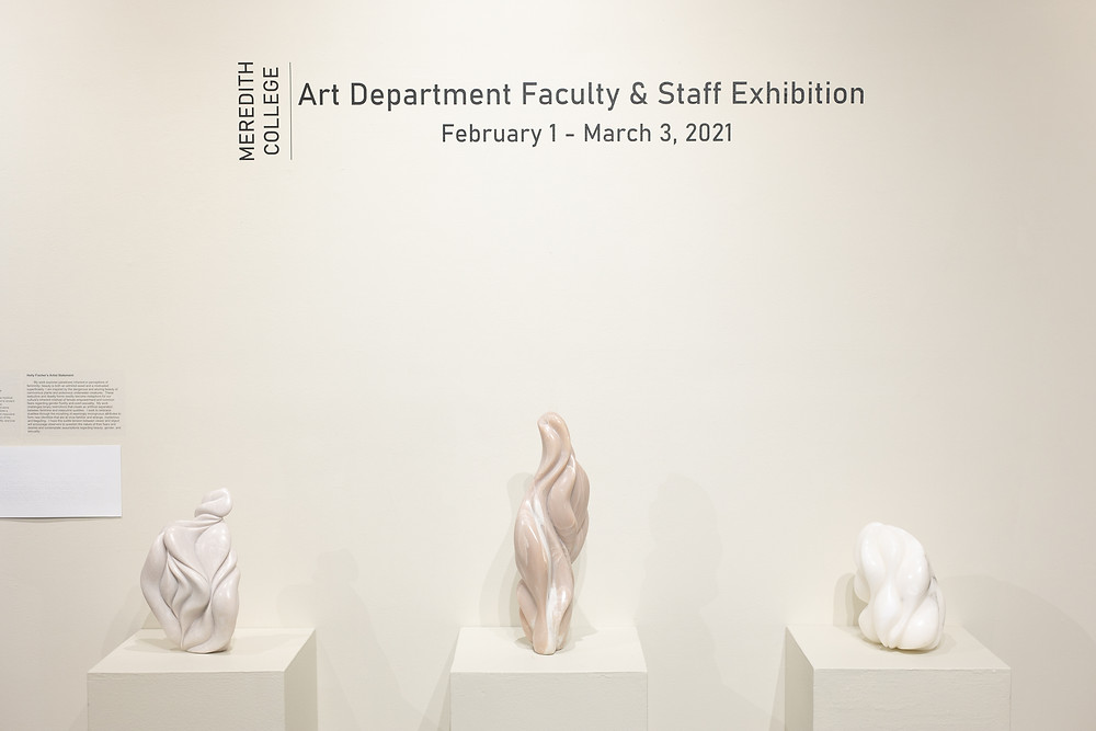 "Image depicting a trio of three pink-and-white sculptures in front of a sign reading ""Art Department Faculty & Staff Exhibition: February 1 - March 3, 2021"""