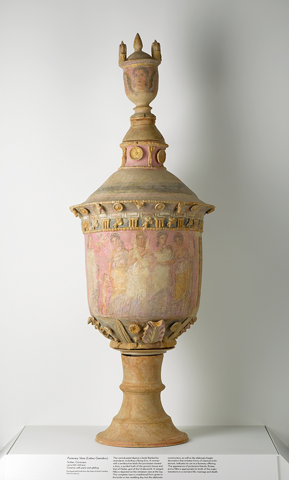 The funerary vase, which is beige with a pinkish hue where figures are depicted