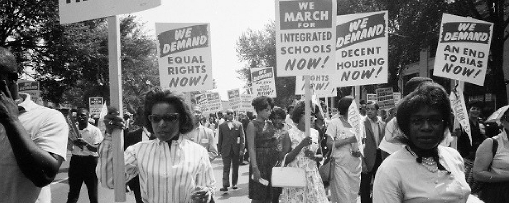 Black-and-white photo of people marching in the streets during the Civil Rights Movement