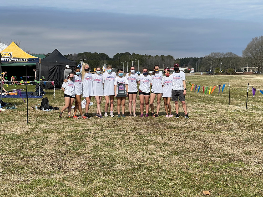 The cross country team standing together with masks on