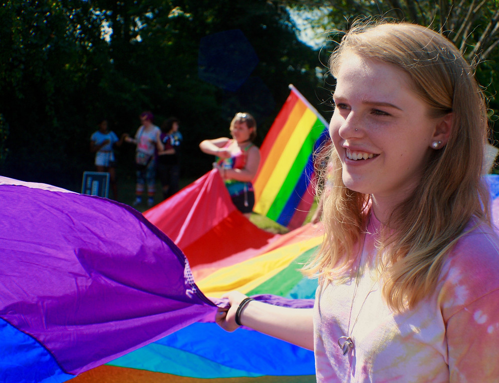 A blonde girl standing with a pride flag