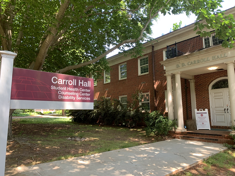 The front entrance and sign in front of Carroll Hall