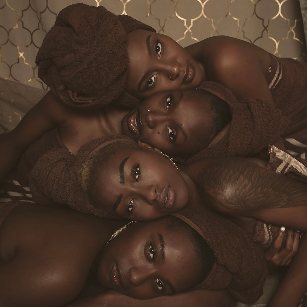 Four Black women laying against each other with mainly their faces in-frame