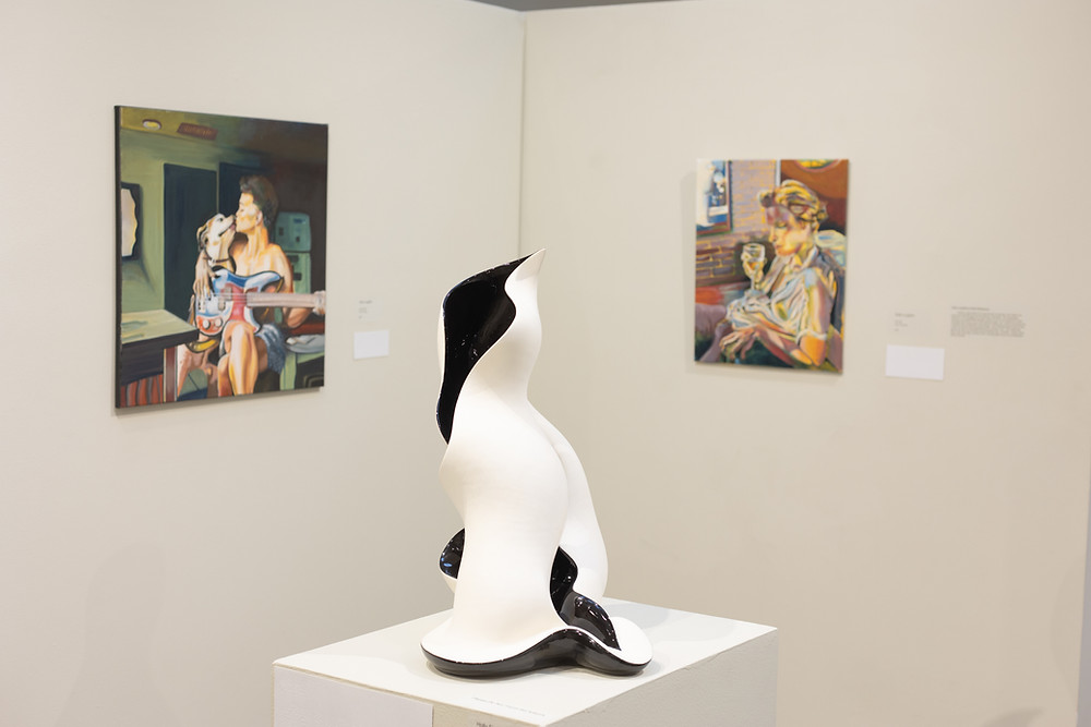 Black and white sculpture in the foreground, two drawings of women in the background.