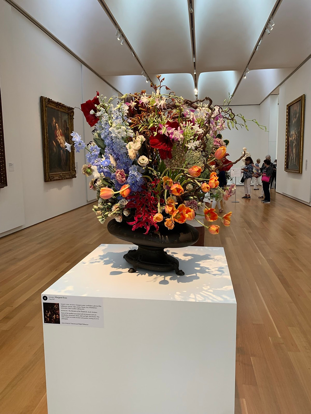 A vase with blue, orange, red, and pink flowers