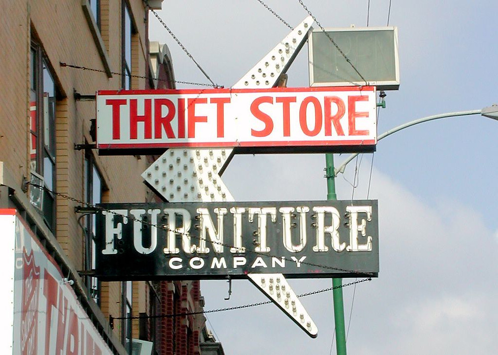 """A sign saying """"thrift store"""" on the side of a brick building"""