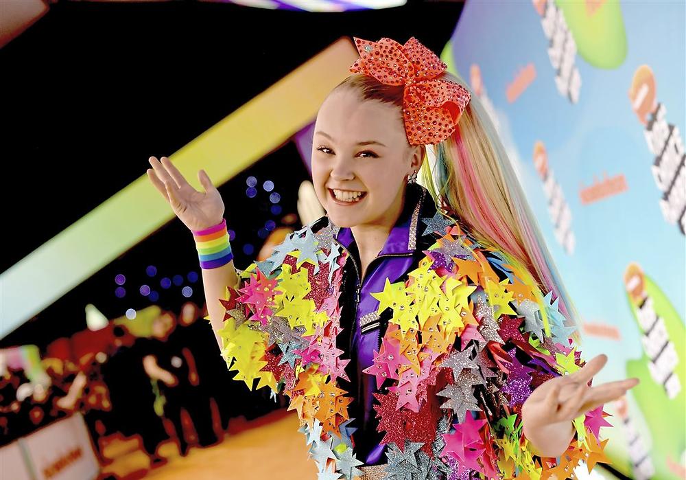 JoJo Siwa in a rainbow star-covered jacket and a rainbow bracelet on one wrist