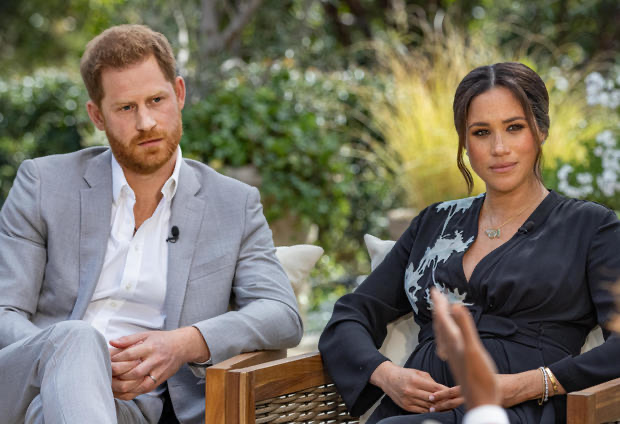 Prince Harry and Meghan Markle sitting next to each other outside where the interview with Oprah took place