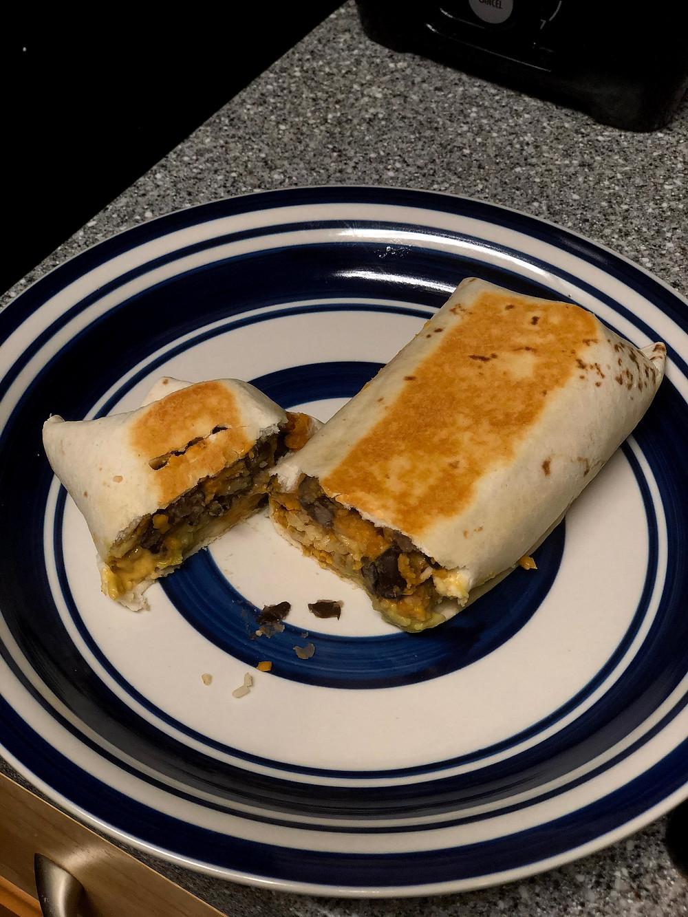 A cut, golden-brown sweet potato and black bean burrito